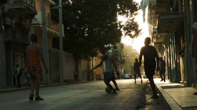 Silhouettes of children playing soccer on the sidewalk in Havana