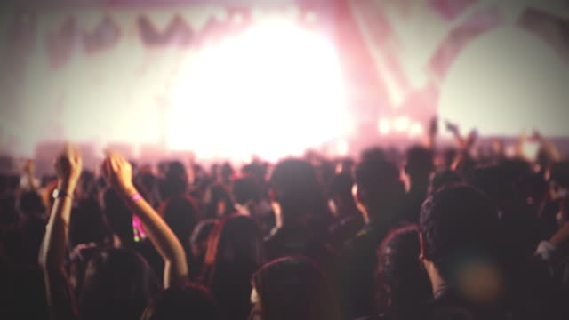 silhouettes of concert crowd at Rear view of festival crowd raising their hands on bright stage lights video