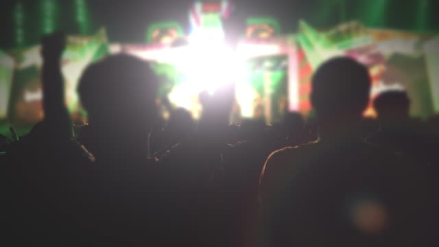 silhouettes of concert crowd at Rear view of festival crowd raising their hands on bright stage lights