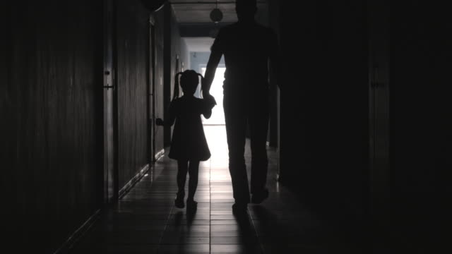 Silhouettes of Dad and Daughter with Balloon Walking along Corridor