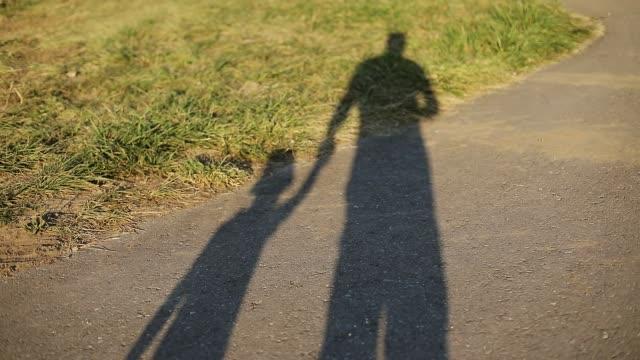 silhouettes of dad and son on asphalt in summer. - syn filmów i materiałów b-roll