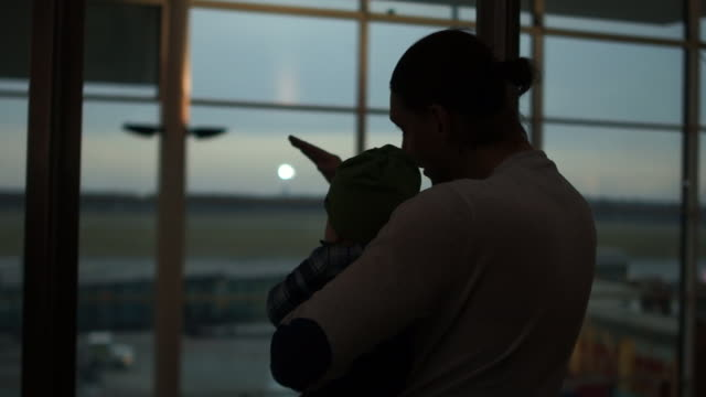 silhouettes of father and son looking at airplanes. the surprised kid looks like dad shows by hand how the plane takes off. kids development - заколоченный стоковые видео и кадры b-roll