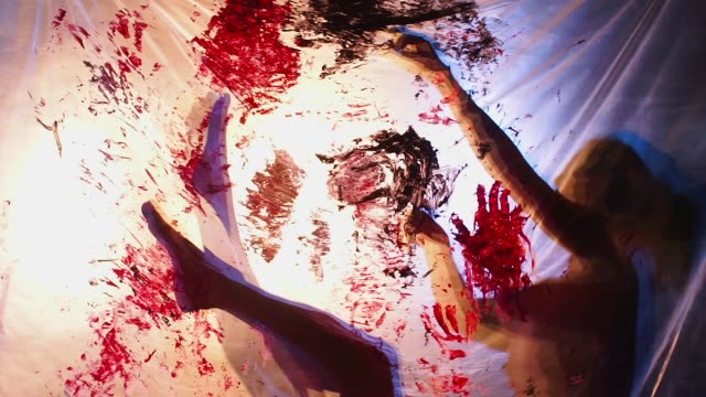 Silhouettes of female hands and feet on a film with spots of paint.