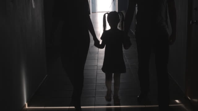 Silhouettes of Girl Holding Balloon Walking along Hallway with Parents