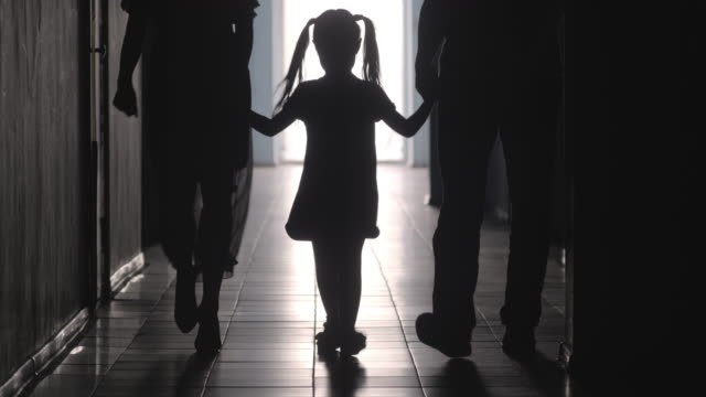 Silhouettes of Girl Holding Hands with Parents and Walking along Hallway