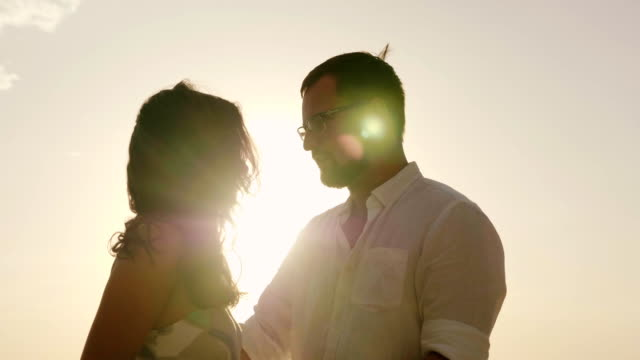 Silhouettes of man and woman kissing against the sky in a hot sunny day video