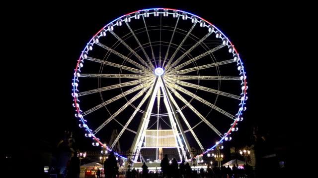vídeos y material grabado en eventos de stock de siluetas de muchas personas que visitan el parque de diversiones para observación rueda de viaje - noria