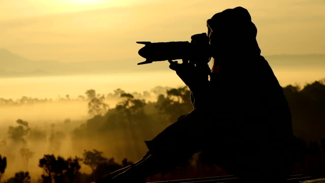 Silhouettes of Nature photographer in action,slow motion video