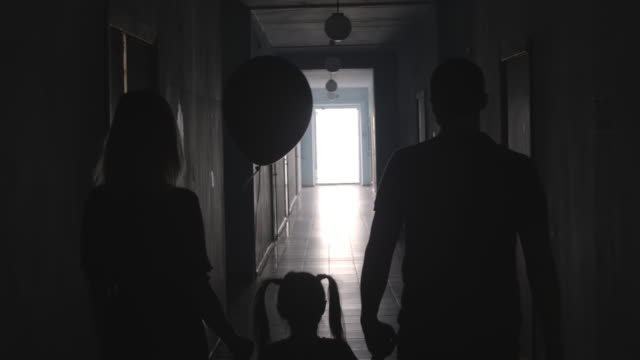 Silhouettes of Parents and Little Daughter with Balloon Going along Hallway