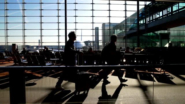 силуэты пассажиров, идущих и сидящих в терминале аэропорта, путешествия - аэровокзал стоковые видео и кадры b-roll