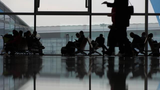 stockvideo's en b-roll-footage met silhouetten van passagiers die in luchthaven lopen. - vliegveld vertrekhal