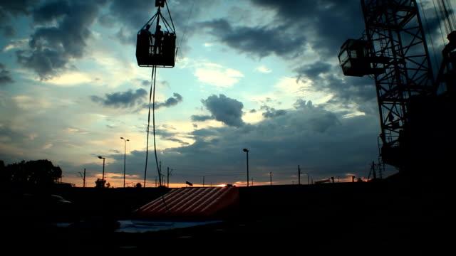 下に行く人々 のシルエット クレーン、夕暮れの工事現場でのプラットフォーム ビデオ