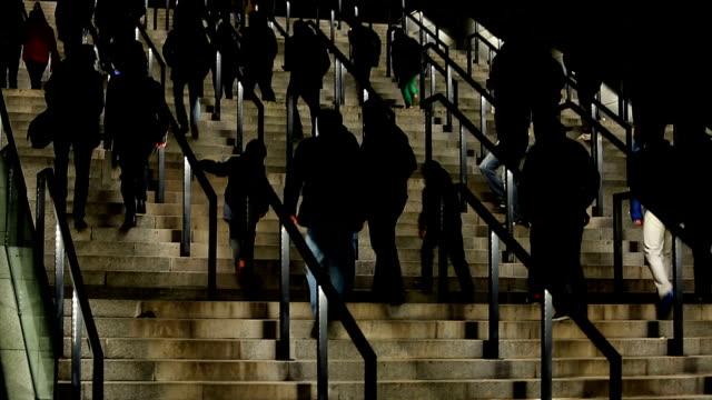 vidéos et rushes de silhouettes de personnes marchant à l'étage, entrée stade foule, touristes - lieu sportif