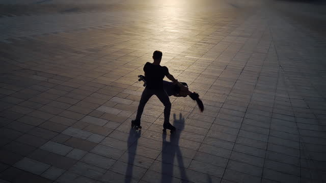 Silhouettes of roller skaters performing extreme tricks at sunset