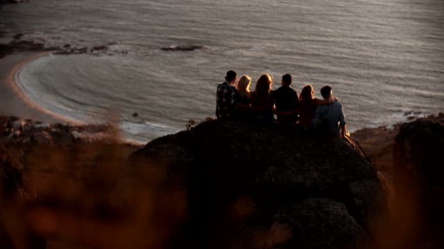 Silhouettes of teens sitting watching the sun set over ocean Silhouettes of teenagers sitting together on rocks watching the sunset peacefully over the ocean in Slow Motion group of objects stock videos & royalty-free footage