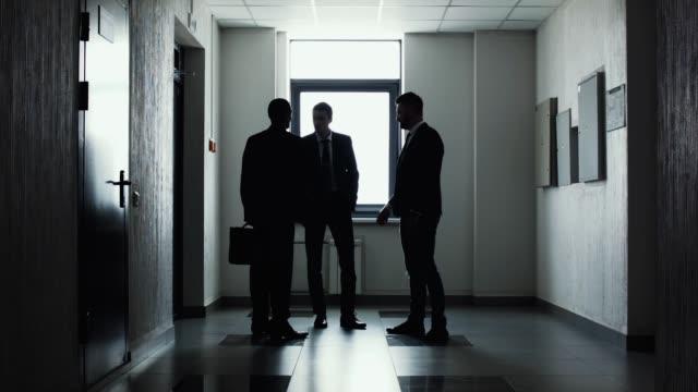 vidéos et rushes de silhouettes de trois hommes d'affaires. poignée de main. - costume habillé