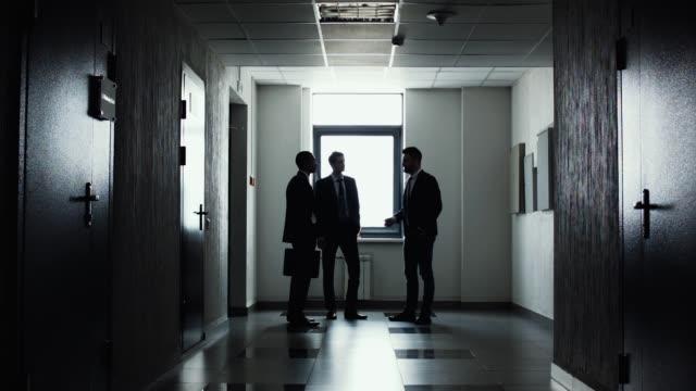 vídeos de stock e filmes b-roll de silhouettes of three businessmen. - três pessoas