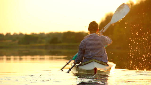 Silhouettes of tourists paddling kayak, teamwork, togetherness video