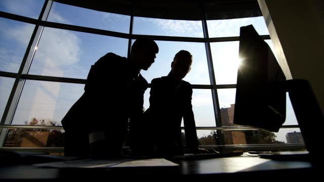 Silhouettes of two businessmen working with a computer on a window background in a big bright office video