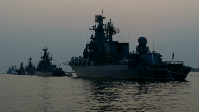 silhouettes of warships of the fleet in the evening sea video