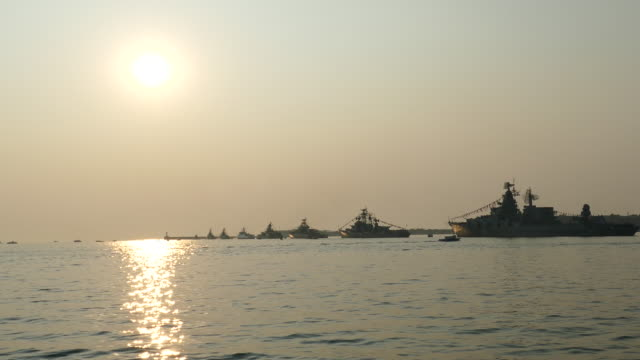 silhouettes of warships on the background of the sun video