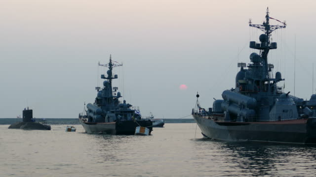 silhouettes of warships on the evening sea video
