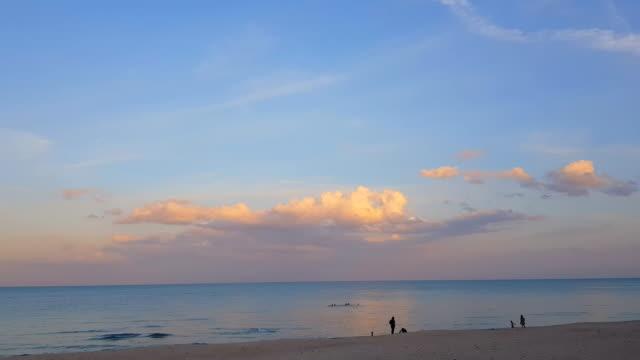 stockvideo's en b-roll-footage met silhouetten van jonge groep mensen springen in strand bij zonsondergang - grace bay