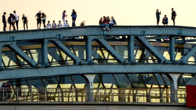 silhouetten von jungen menschen flanieren und die bilder von einander in einer prekären situation auf der oberseite der brücke, zeitraffer - stuntman stock-videos und b-roll-filmmaterial