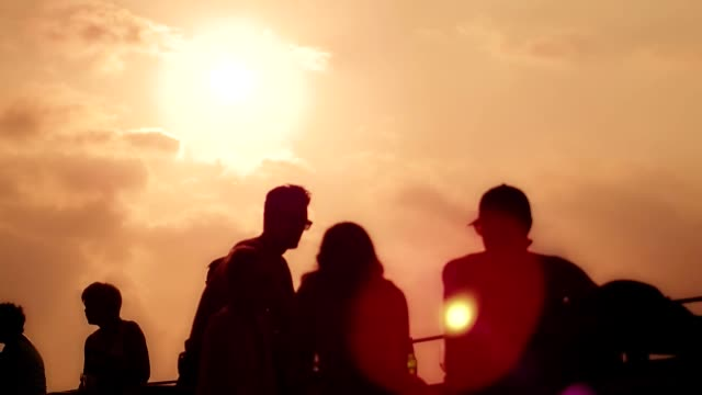 Silhouettes people resting and talking in evening cafe on sunset background video