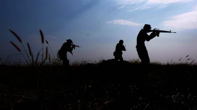 силуэты, отряд полностью оборудованных и вооруженных солдат, идущих в одном файле в лесу - рядовой стоковые видео и кадры b-roll