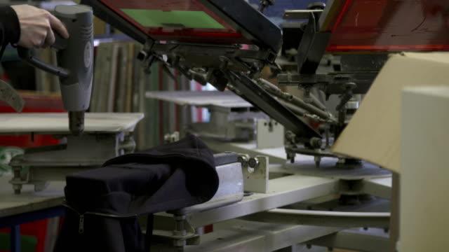 Silk Screen Fashion Printing A logo design being printed at a silk screen studio shirt stock videos & royalty-free footage
