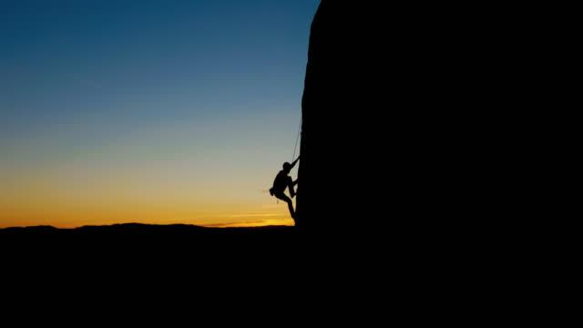 stockvideo's en b-roll-footage met sillhouette rock climbing - touw