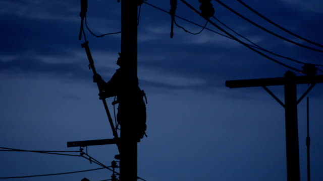 sillouette electrician lineman repairman worker at climbing work on electric post power pole video