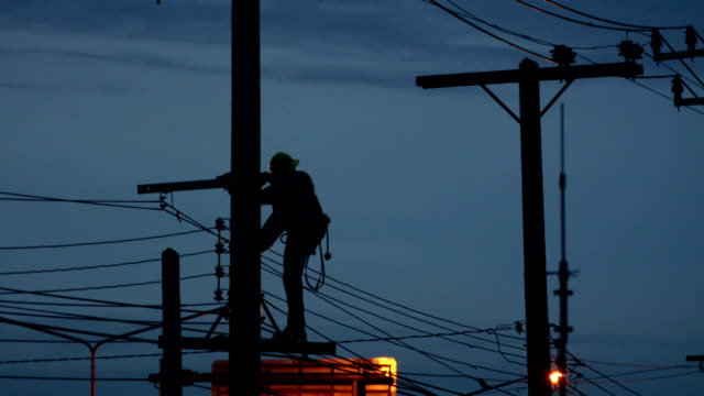 sillouette electrician lineman repairman worker at climbing work on electric post power pole