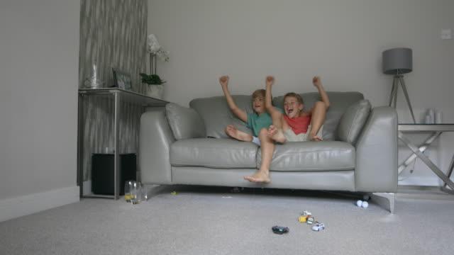 silly brothers watching tv - предподростковый возраст стоковые видео и кадры b-roll