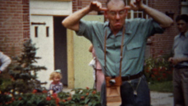 1940: Silly photographer man making funny faces at camera. video