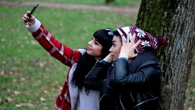 Silly young girlfriends taking a selfie leaning on a tree video