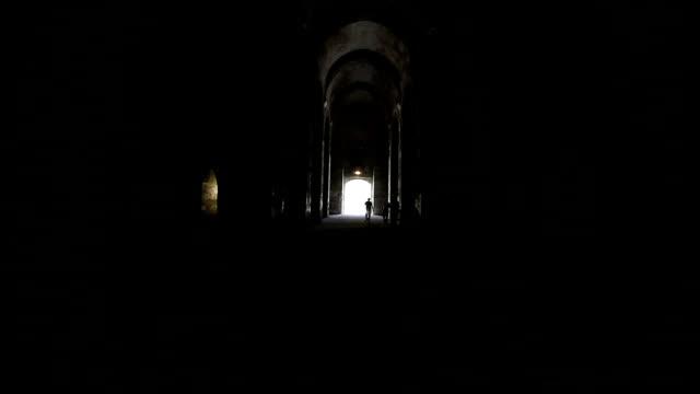 Silouette Of People Walking Toward Exit In Dark Alley video