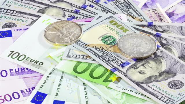 argento dollaro americano monete su sfondo di banconote di grosso taglio diverso - simbolo della sterlina video stock e b–roll
