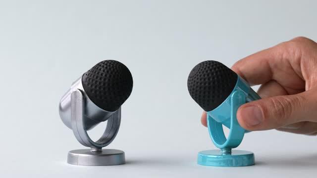 vidéos et rushes de microphone argenté et bleu sur le fond blanc - interview