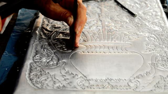 Silver art handicrafts of Lanna, Thai style, Chiang Mai, Thailand, hand banging on silver with a hammer. video