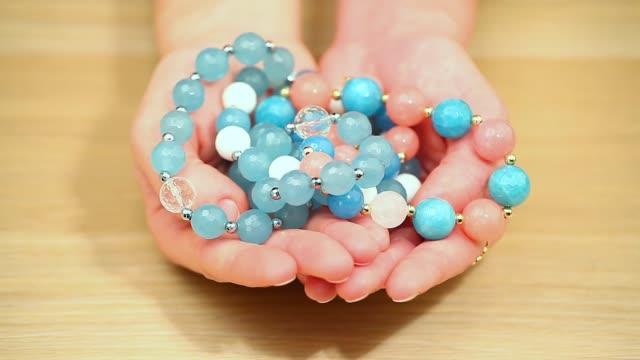 silver blue agate ceramic bracelet stones woman hands hd footage wooden table nobody - браслет стоковые видео и кадры b-roll