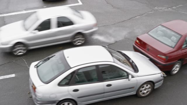 Silver car crashing into ta red car in front and driver stepping out