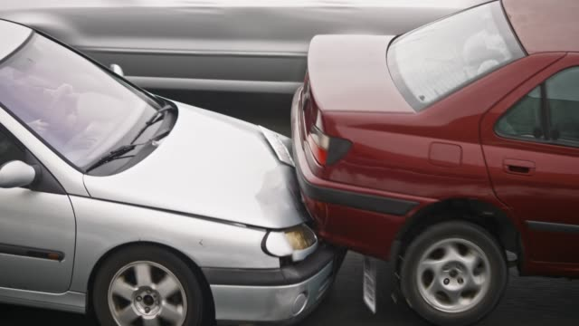 silver car hitting the red car from behind - incidente video stock e b–roll
