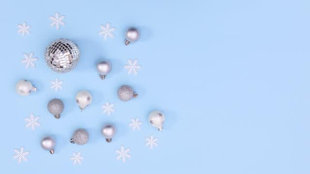 vídeos de stock e filmes b-roll de silver christmas ornaments and snowflakes appear on pastel blue theme. stop motion - animação em stop motion