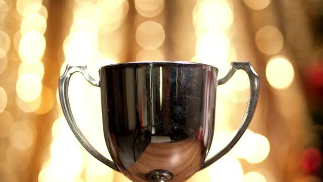 vídeos de stock, filmes e b-roll de troféu de prata com fundo de luz natalina, conceito de vitória. - troféu