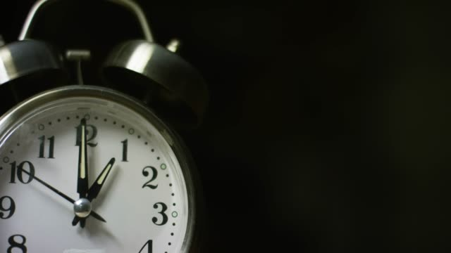 A Silver-Colored, Metal, Retro-Style, Analog Alarm Clock at 1:00