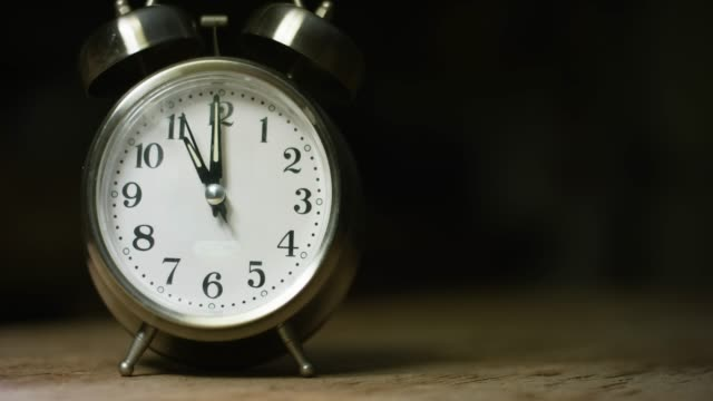 A Silver-Colored, Metal, Retro-Style, Analog Alarm Clock at 11:00