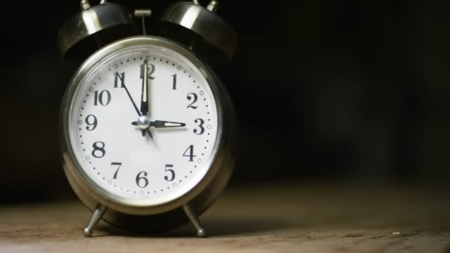 A Silver-Colored, Metal, Retro-Style, Analog Alarm Clock at 3:00