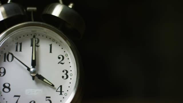 A Silver-Colored, Metal, Retro-Style, Analog Alarm Clock at 4:00